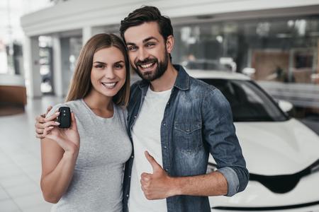 Foto de Happy beautiful couple is choosing a new car at dealership, smiling and looking at camera. - Imagen libre de derechos