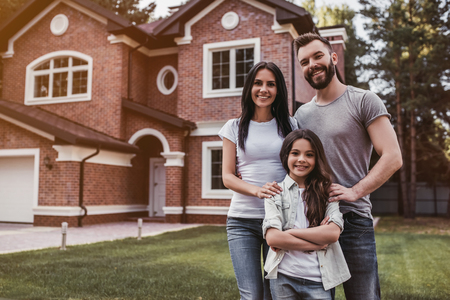 Photo pour Happy family is standing near their modern house, smiling and looking at camera. - image libre de droit