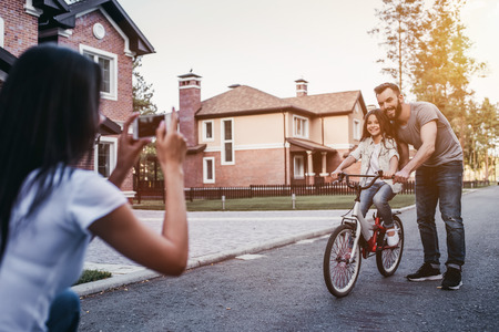 Photo pour Dad is teaching daughter how to ride bicycle. Mother is taking photo on a smart phone. - image libre de droit