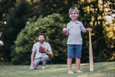 Photo pour Handsome dad with his little cute sun are playing baseball on green grassy lawn - image libre de droit