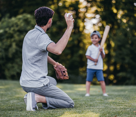 Photo for Handsome dad with his little cute sun are playing baseball on green grassy lawn - Royalty Free Image