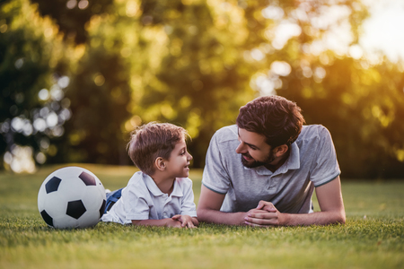 Foto de Handsome dad with his little cute sun are playing football on green grassy lawn - Imagen libre de derechos