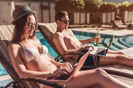 Foto de Working even on vacation! Young couple in sunglasses are lying on a chaise-longues near swimming pool with laptops. - Imagen libre de derechos