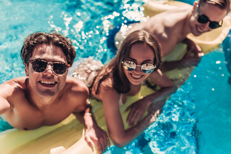 Foto de Happy attractive young friends in sunglasses are having fun in swimming pool on an inflatable mattress and smiling while making selfie. - Imagen libre de derechos