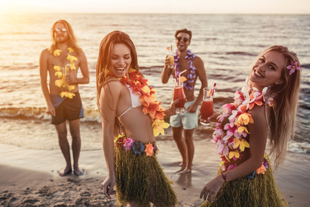 Photo for Group of young attractive friends are having fun on beach, drinking cocktails, dancing and smiling. Party in Hawaiian style. - Royalty Free Image