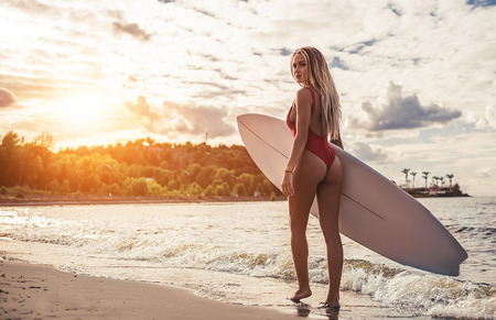 Photo pour Attractive sexy young woman in red swimsuit is standing on beach with white surfboard in hands. - image libre de droit