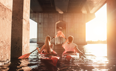 Foto de Beautiful young couple is kayaking on river. Waiting for the sunset. Canoeing together - Imagen libre de derechos
