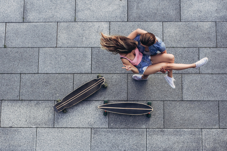 Photo pour Top view of young teenager couple with longboards is having fun in the city. - image libre de droit