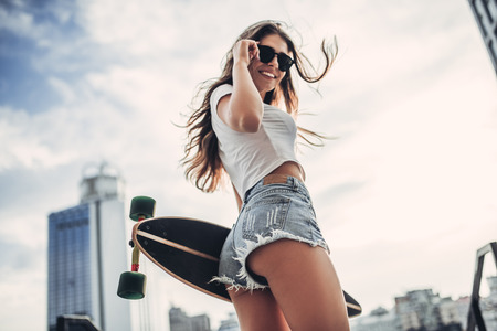 Photo pour Young woman is posing with skateboard in the city. Female teenager outdoor with longboard. - image libre de droit