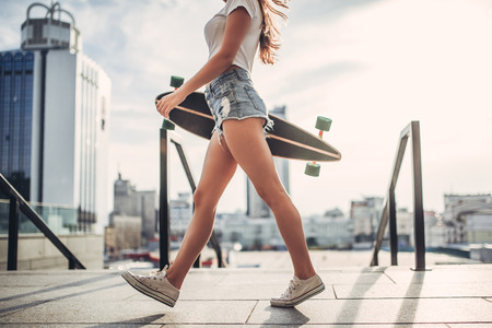 Photo pour Cropped image of young woman is posing with skateboard in the city. Female teenager outdoor with longboard. - image libre de droit