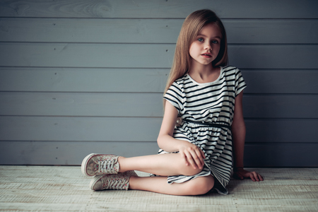 Photo pour Charming little girl is sitting on the floor on grey background with  perceptive glance. Cute girl posing - image libre de droit
