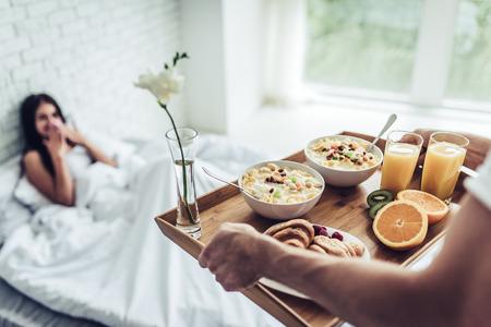 Foto de Good morning! Healthy breakfast in bed. Beautiful young woman is lying in bed while her handsome man bringing tasty breakfast. - Imagen libre de derechos