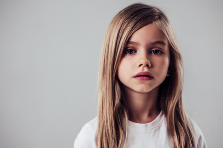 Photo pour Little cute girl isolated. Charming blonde is posing on white background and looking at camera. - image libre de droit