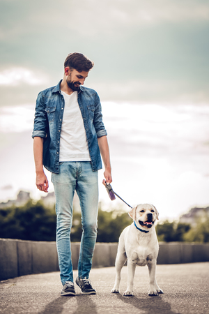 Photo pour Handsome young man with labrador outdoors. Man on a walk in the city with his dog. - image libre de droit