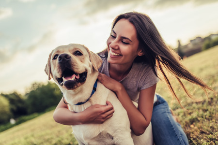 Foto de Attractive young woman with labrador outdoors. Woman on a green grass with dog labrador retriever. - Imagen libre de derechos