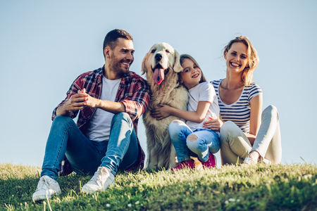 Photo pour Beautiful happy family is having fun with golden retriever outdoors. Mother, father and daughter are sitting with dog labrador on green grass in park. - image libre de droit