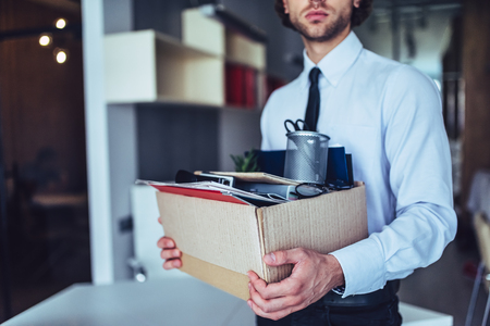 Photo for Young handsome businessman in light modern office with carton box. Last day at work. Upset office worker is fired. - Royalty Free Image