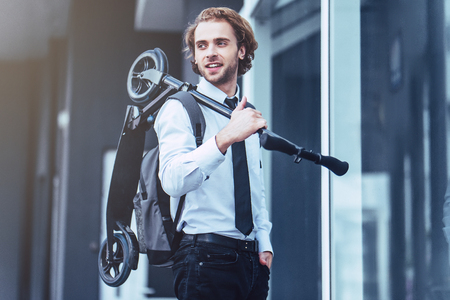 Photo for Young handsome businessman on street with kick scooter. - Royalty Free Image