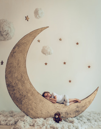 Photo pour Sweet dreams. Little cute girl with plush toy is sleeping on artificial Moon with cotton clouds and stars - image libre de droit