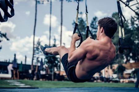 Foto de Handsome muscular man is training outdoor on TRX. Total Body Resistance Exercises. Working out at gym. - Imagen libre de derechos