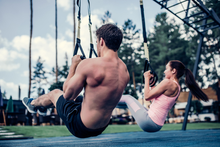 Foto de Young couple are training outdoor on TRX. Total Body Resistance Exercises. Attractive woman and handsome man are working out at gym. - Imagen libre de derechos