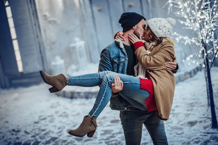 Photo pour Young romantic couple is having fun outdoors in winter before Christmas. Enjoying spending time together in New Year Eve. Two lovers are hugging and kissing in Saint Valentine's Day. - image libre de droit