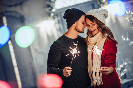 Photo for Young romantic couple is having fun outdoors in winter before Christmas with Bengal lights. Enjoying spending time together in New Year Eve. Two lovers are hugging and kissing in Saint Valentine's Day - Royalty Free Image