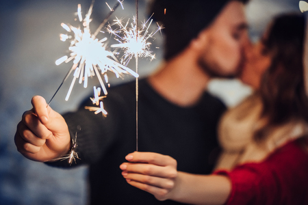 Foto de Young romantic couple is having fun outdoors in winter before Christmas with Bengal lights. Enjoying spending time together in New Year Eve. Two lovers are hugging and kissing in Saint Valentine's Day - Imagen libre de derechos