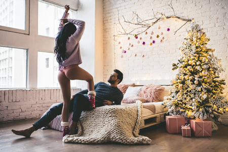 Photo pour Passionate romantic couple is spending time together before New Year near beautiful Christmas tree at home - image libre de droit