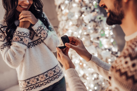 Foto de Merry Christmas and Happy New Year! Beautiful couple is waiting for the New Year together near beautiful Christmas tree at home. Handsome man is making proposal to his attractive young woman. - Imagen libre de derechos