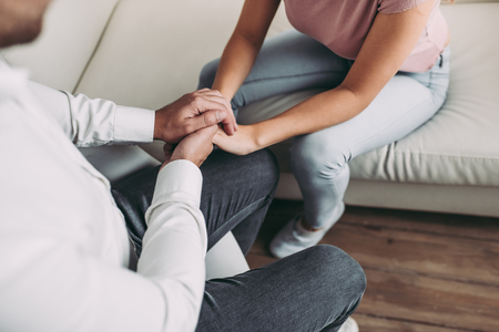 Foto de Cropped image of young woman is sitting on sofa during the psychotherapy session. Girl at a psychologist's reception. Experianced doctor is sitting nearby and holding patient's hands. - Imagen libre de derechos