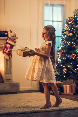 Foto de Little cute girl in dress is waiting for Christmas at home. Charming kid in New Year Eve with gift box in hands. - Imagen libre de derechos