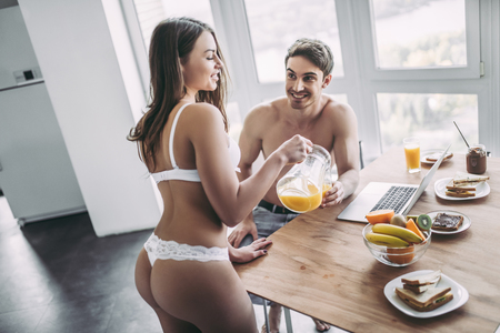 Photo for Good morning! Young romantic couple is having breakfast on modern light kitchen. Handsome man is sitting at the table with laptop while his sexy woman is standing nearby in underwear with orange juice. Healthy lifestyle concept. - Royalty Free Image