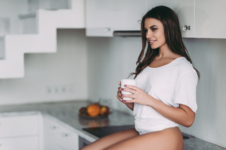 Photo for Good morning! Young sexy woman in underwear is sitting on light modern kitchen with cup of coffee in hands and smiling. - Royalty Free Image