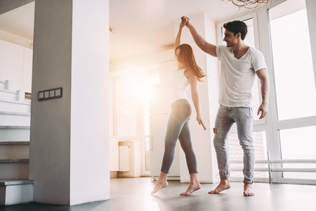 Foto de Romantic couple at home. Attractive young woman and handsome man are enjoying spending time together. Passionate couple is dancing on light modern kitchen with paniramic windows. - Imagen libre de derechos