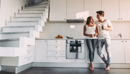 Foto de Full-length image of romantic couple at home. Attractive young woman and handsome man are enjoying spending time together while standing on light modern kitchen with cup of coffee in hands. - Imagen libre de derechos