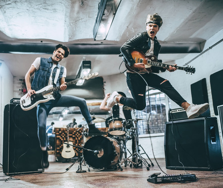 Photo for Repetition of rock music band. Bass guitar player, electro guitar player and drummer behind the drum set. Rehearsal base - Royalty Free Image