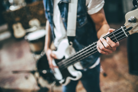 Photo for Repetition of rock music band. Cropped image of bass guitar player. Rehearsal base - Royalty Free Image