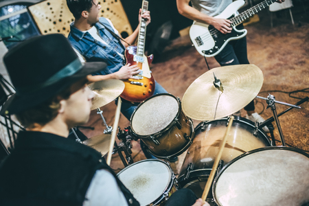 Photo for Repetition of rock music band. Cropped image of bass guitar player, electro guitar player and drummer behind the drum set. Rehearsal base - Royalty Free Image