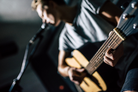 Photo for Cropped image of handsome young man on rehearsal base. Lyric singer with acoustic guitar. - Royalty Free Image