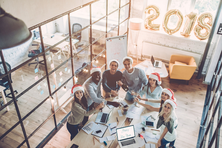 Photo pour Merry Christmas and Happy New Year 2018! Top view of multiracial young creative people are celebrating holiday in modern office. - image libre de droit