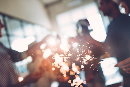 Foto de Merry Christmas and Happy New Year 2018!Multiracial young creative people are celebrating holiday in modern office. Cropped image of group of young business people are drinking champagne with sparkling bengal lights in coworking. - Imagen libre de derechos