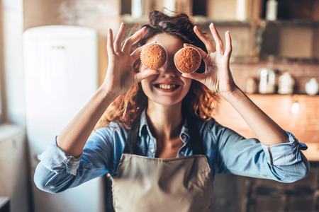 Foto de Attractive young woman is cooking on kitchen. Having fun while making cakes and cookies. - Imagen libre de derechos