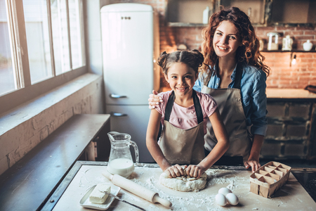 Photo for Attractive young woman and her little cute daughter are cooking on kitchen. Having fun together while making cakes and cookies. Smiling and looking at camera. - Royalty Free Image