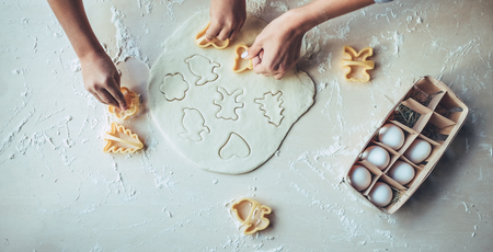 Foto de Cropped image of attractive young woman and her little cute daughter are cooking on kitchen. Having fun together while making cakes and cookies. - Imagen libre de derechos
