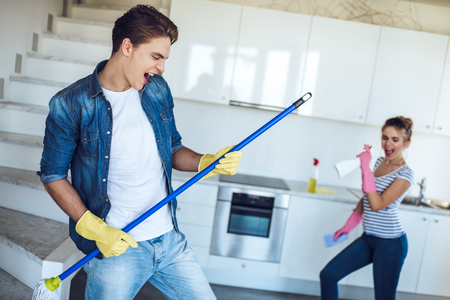 Foto de Young happy couple is having fun while doing cleaning at home. - Imagen libre de derechos