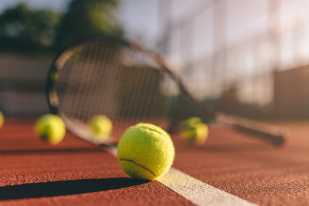 Foto de Balls and racket are lying on brown tennis court. - Imagen libre de derechos