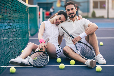 Photo pour Young couple is sitting on tennis court. Handsome man and attractive woman are playing tennis. - image libre de droit