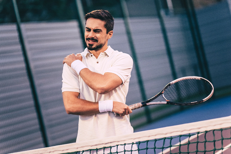 Photo pour Handsome man on tennis court. Young tennis player. Shoulder pain - image libre de droit