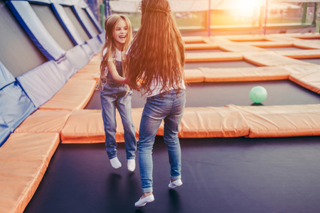 Foto de Little pretty girls having fun outdoor. Jumping on trampoline in children zone. Amusement park - Imagen libre de derechos
